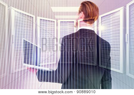 Businessman looking up holding laptop against digitally generated server room with towers