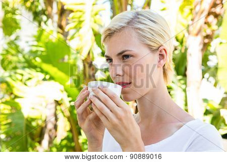 Attractive blonde woman drinking hot beverage outside on a sunny day