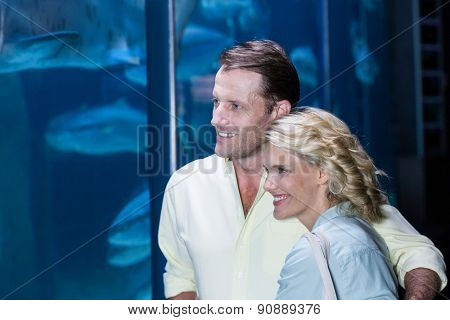 Happy couple looking at fish tank at the aquarium