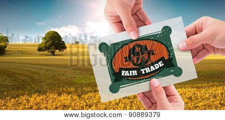 Hand showing card against field with tree and city on the horizon