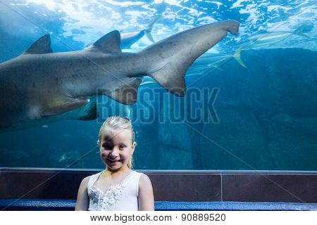 Young woman behind a shark tank looking at camera at the aquarium