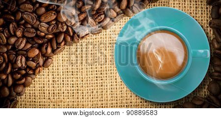 Blue cup of coffee against coffee beans and burlap sack