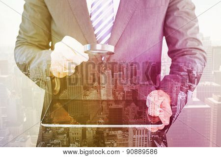 Businessman looking at tablet with magnifying glass against high angle view of city