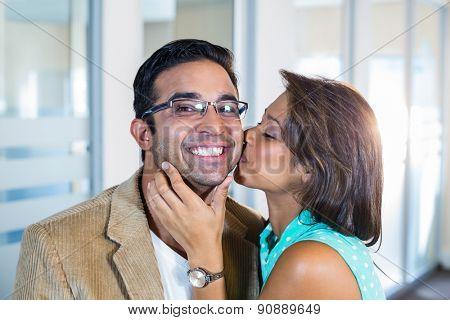 Beautiful brunette kissing her boyfriend in the office