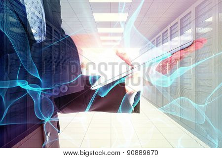 Businessman using his tablet pc against digitally generated server room with towers