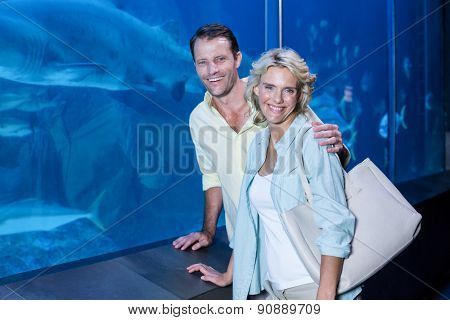 Happy couple looking at camera beside the fish tank at the aquarium