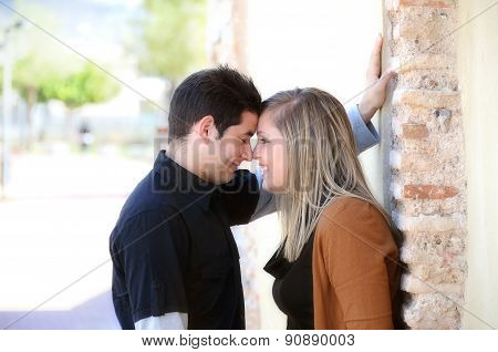 Young Couple Flirting Against A Brick Wall In A Park