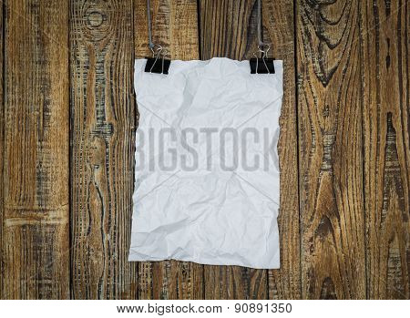 Black clip and White paper hang on wood background