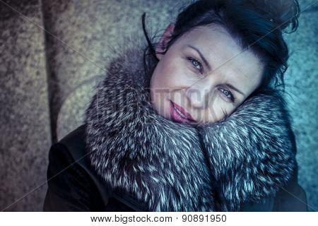 Pretty Russian woman in fur coat in a park in autumn