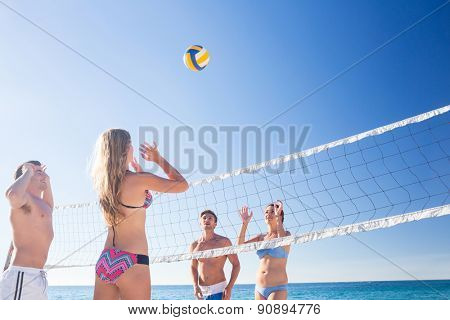 Group of friends playing volleyball at the beach