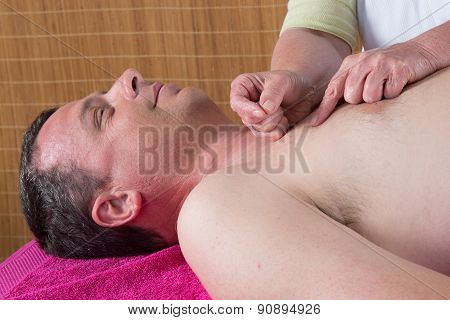 Acupuncturist Prepares To Tap Needle On Man's Torso
