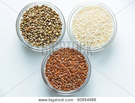 Flax, sesame, and hemp seeds in glass bowls