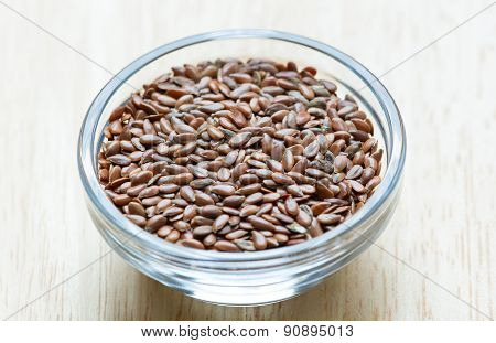 Flax seeds in the glass bowl on a wooden background