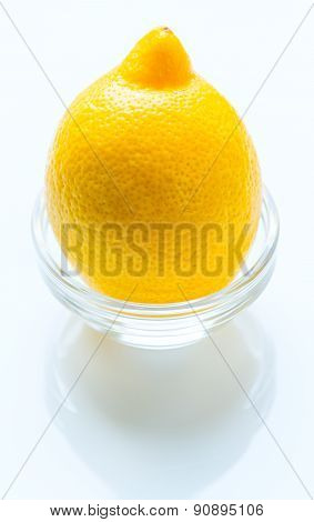 Whole lemon in the glass bowl isolated