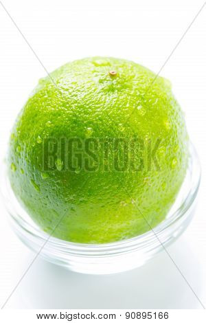 Green lime with water drops in the glass bowl isolated
