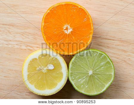Mandarin, lemon, and green lime slices on wooden background
