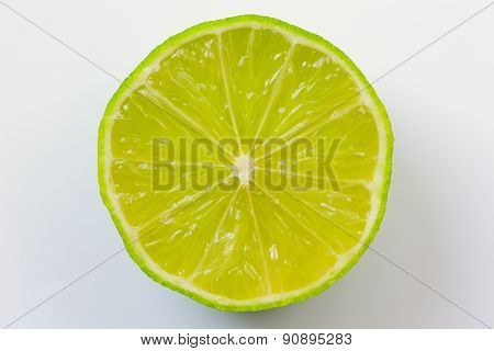 Slice of green lime isolated on white background