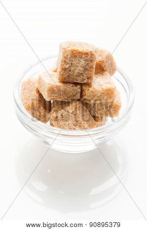 Rushy raw sugar cubes in the glass bowl isolated