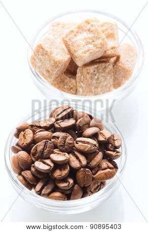 Roasted coffee beans and raw sugar cubes in the glass bowls isolated