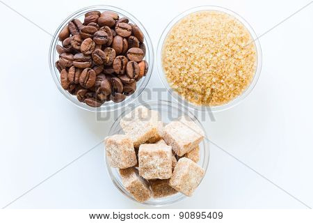 Roasted coffee beans, raw sugar cubes, and brown sugar in the glass bowls isolated