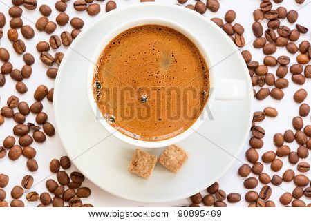 Fresh brewed coffee mug with sugar cubes and coffee beans