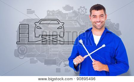 Smiling male mechanic holding lug wrench against grey vignette