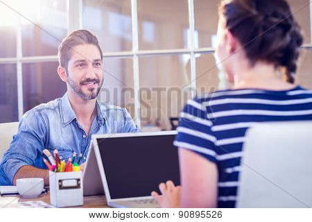 Happy creative workers sharing desk in creative office