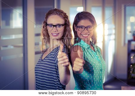 Happy designers showing thumbs up in creative office