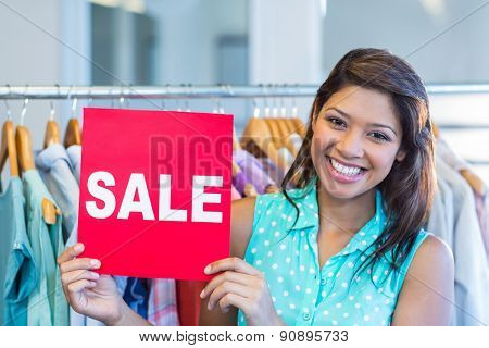 Beautiful brunette holding red sign in clothes store