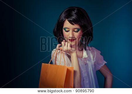 Shopping teen with a bag of orange on blue chroma