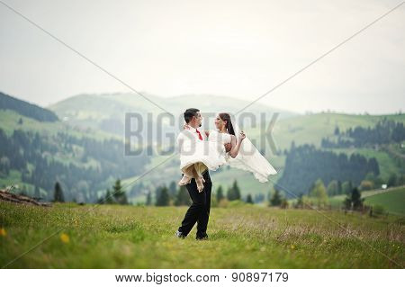 Wedding Couple In The Carpathian Mountains. Groom Holds A Bride
