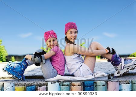 Two Girls In Roller Skates Sitting Side By Side On The Street.