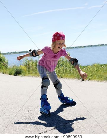 Little Girl Is Learning To Roller Skate. Girl Happily Rolling On Roller Skates.