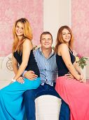 foto of threesome  - happy man embrace two girls on his knees - JPG