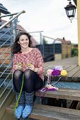 picture of knitting  - young woman sitting outdoors and is knitting - JPG