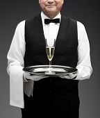 stock photo of flute  - butler with champagne flute on tray on grey background - JPG