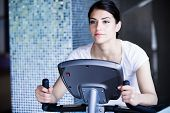 picture of body fat  - Woman riding an exercise bike in gym - JPG