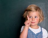 foto of clever  - clever girl in front of black board with forefinger up - JPG