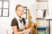 picture of saxophones  - Portrait of girl in school uniform dress with alto saxophone to play in musical school - JPG