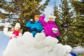 picture of snowball-fight  - Group of kids play snowballs game together standing behind the snow wall fortress with fir forest on the background during winter day - JPG
