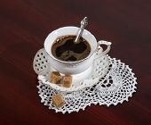 foto of doilies  - cup of coffee and a white lace doily on the table. closeup
