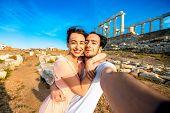 image of poseidon  - Tourist young couple taking selfie portrait on Poseidon temple background in Sounion - JPG