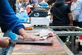 stock photo of paddling  - Fish seller in the fish market of Catania Sicily while cutting a paddle fish into slices - JPG