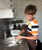 image of homemaker  - boy doing the dishes in the kitchen - JPG