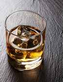 picture of scotch  - Glass of scotch whiskey with ice on black stone table - JPG