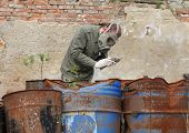 image of nuclear disaster  - Man with gas mask and green military clothes explores dead bird after chemical disaster - JPG
