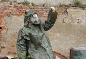 pic of gas mask  - Man with gas mask and green military clothes explores small plant after chemical disaster - JPG