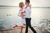 foto of dock  - Wedding beautiful couple in traditional dress on the dock - JPG
