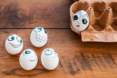 stock photo of egg-laying  - Top view of funny eggs with different emotions flirting with female egg laying in container on the wooden desk  - JPG