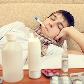 picture of home remedy  - Toned Photo of Sick Teenager on the Sofa at the Home with Pills on foreground - JPG